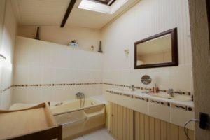 La grande salle de bains avec sa baignoire et sa douche.